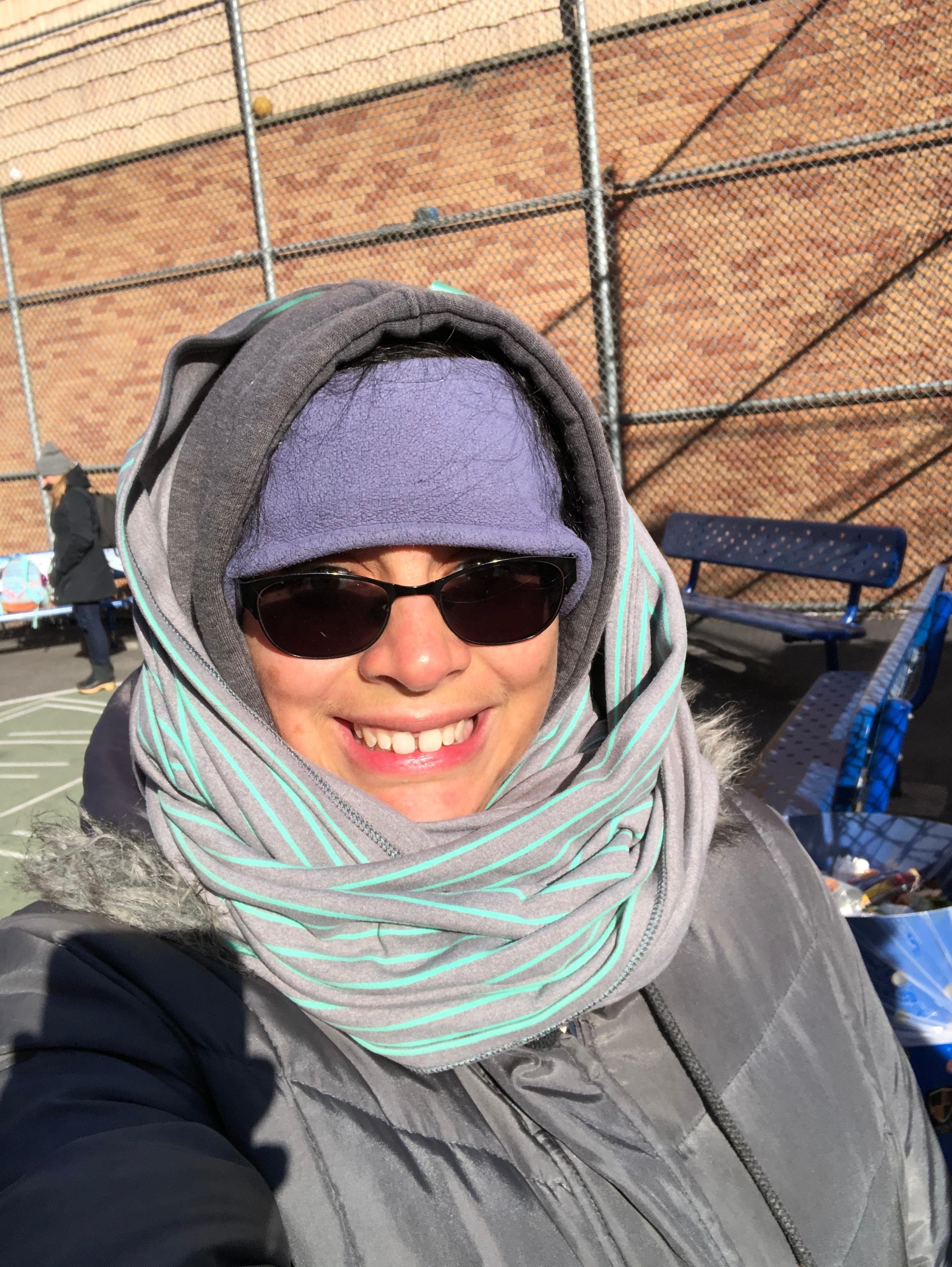 Li Yun Alvarado wearing winter gear: big coat, hoodie, and scarf.