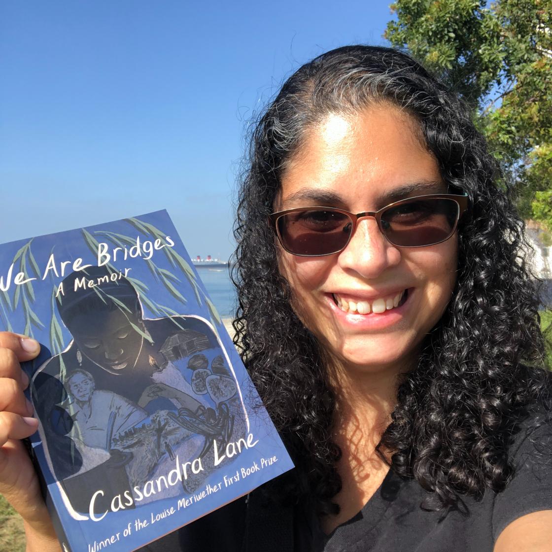 Li Yun holding a copy of WE ARE BRIDGES by Cassandra Lane