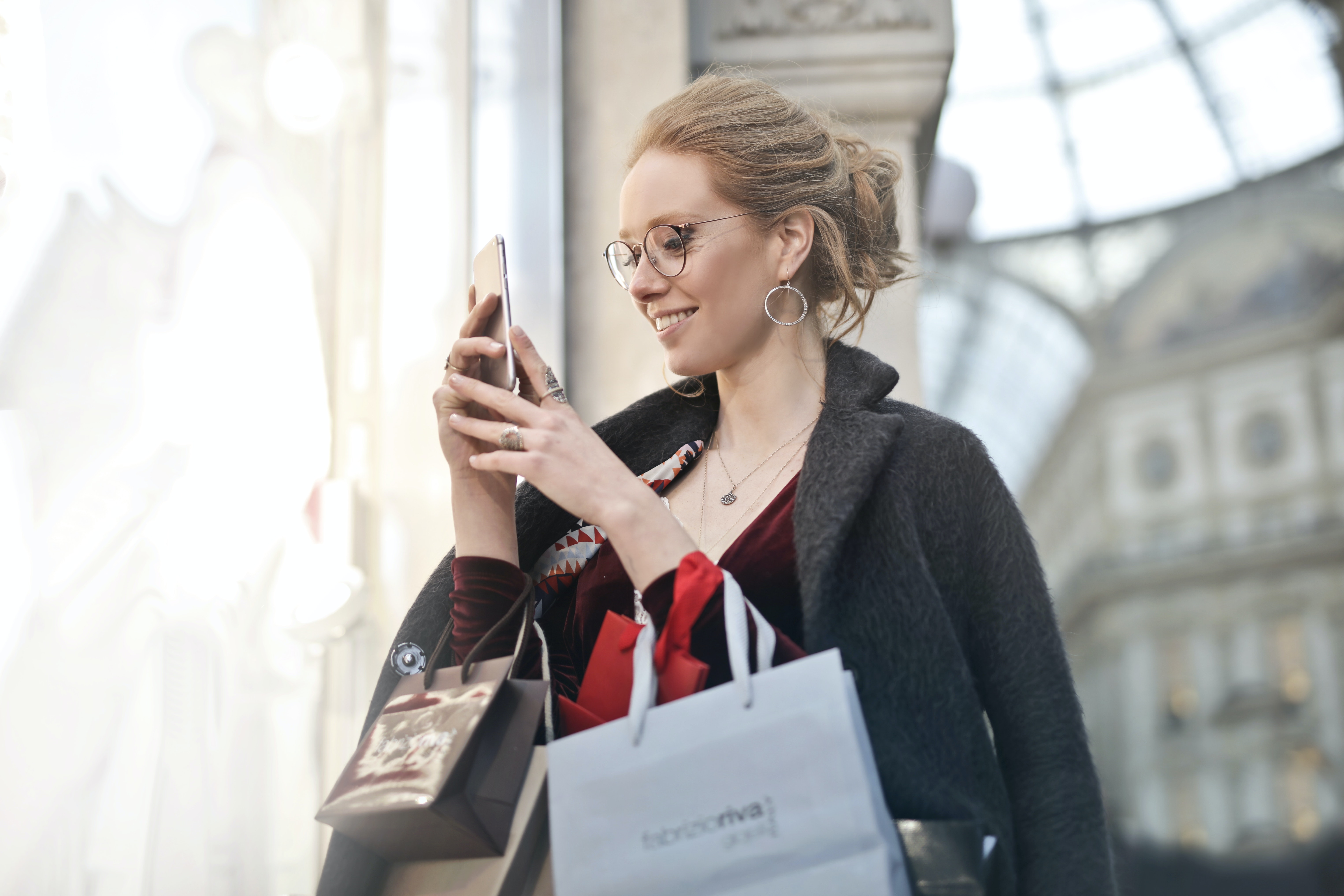 woman holding a mobile phone while shopping