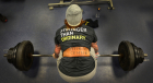 Woman lifting weights wearing tshirt saying 'stronger than ordinary'