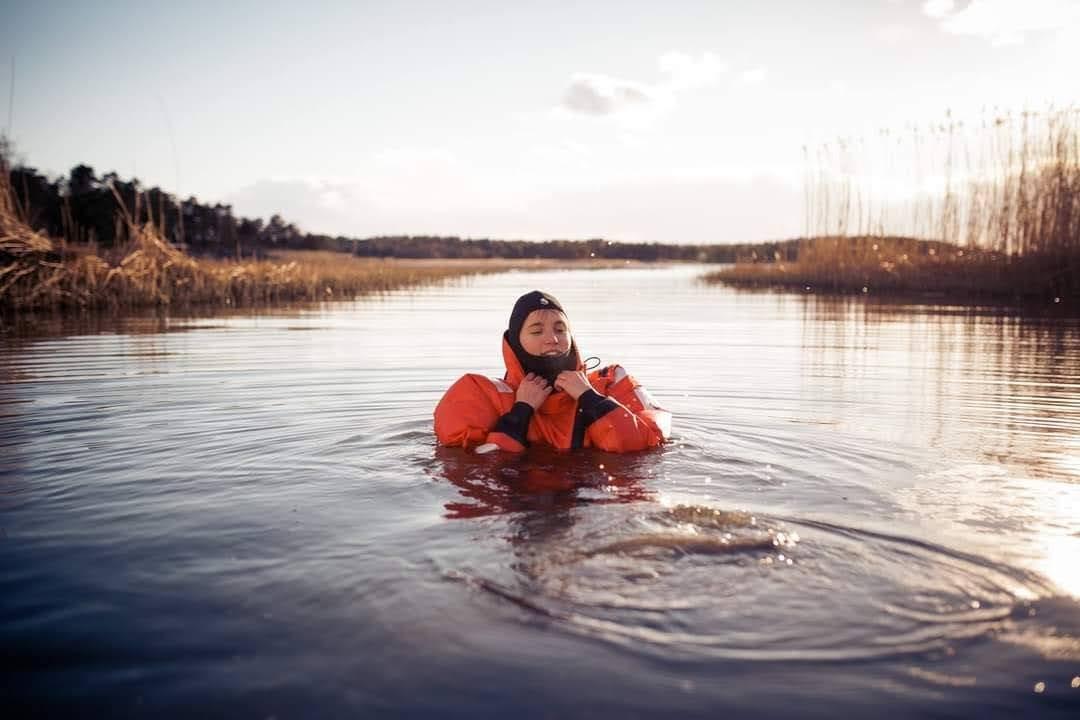 Henkilö pelastautumispuvussa vedessä