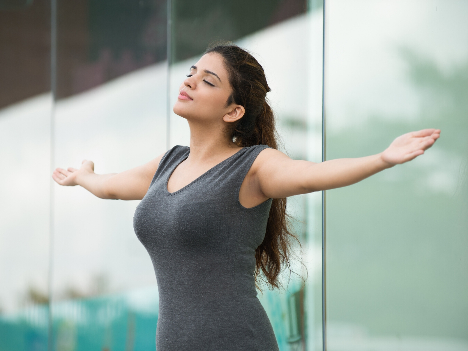 female standing outside with arms wide open praising and worshiping God