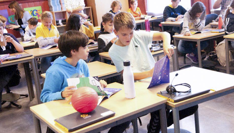 Skolebarn ser i jubileumshefte