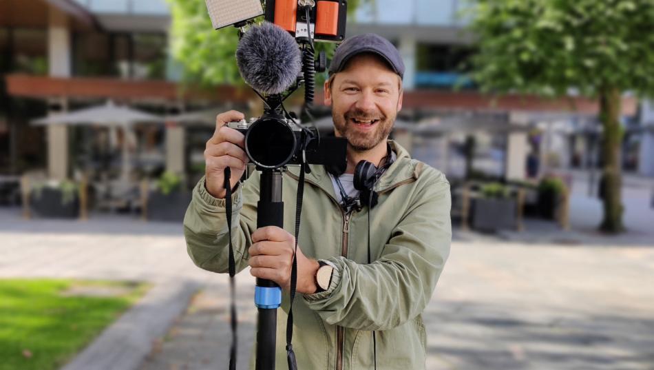 Smilende Petter Uteligger poserer med videokamera