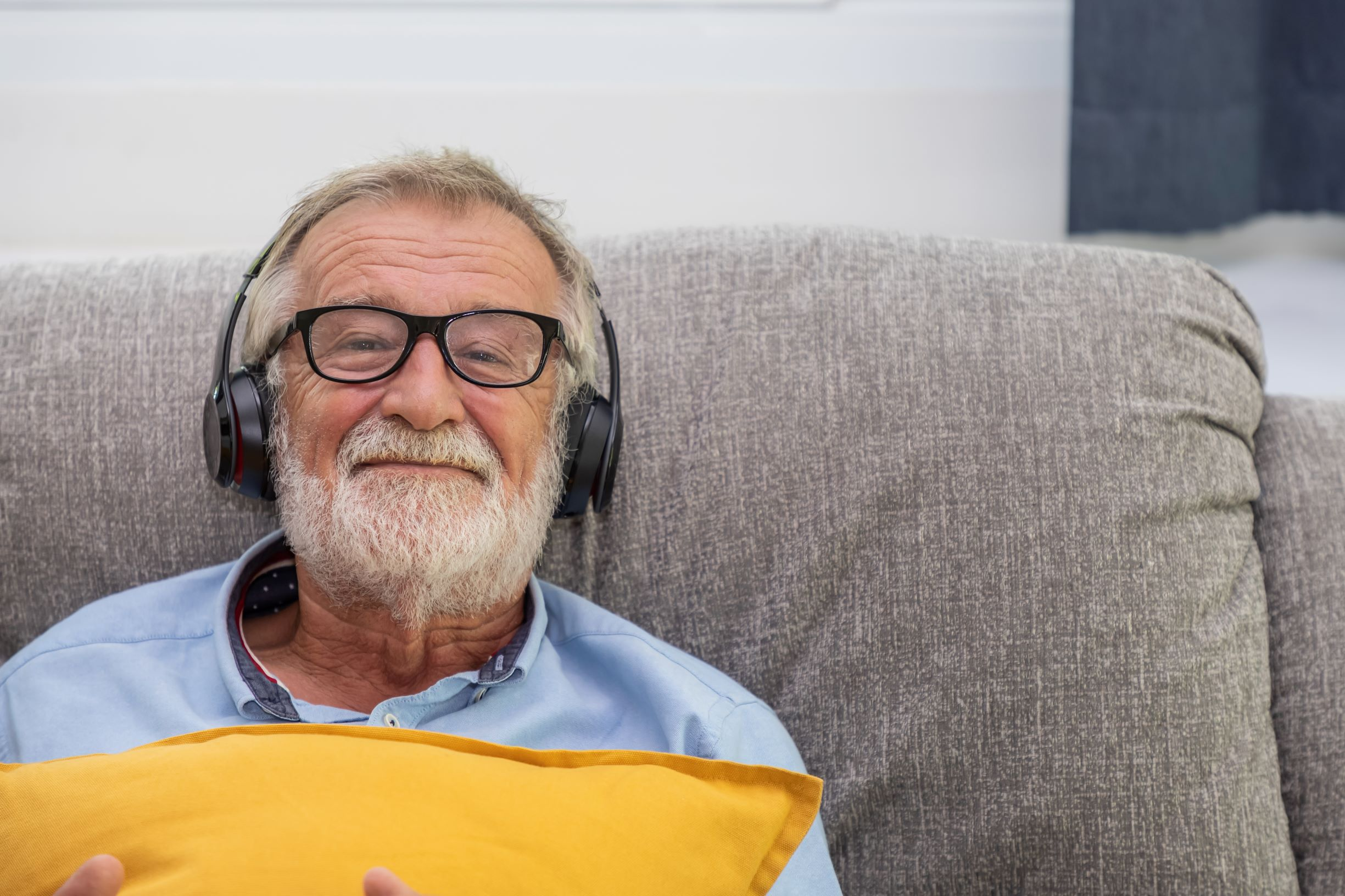 A man sitting on a sofa with headphones on. He is holding a bright yellow cushion.