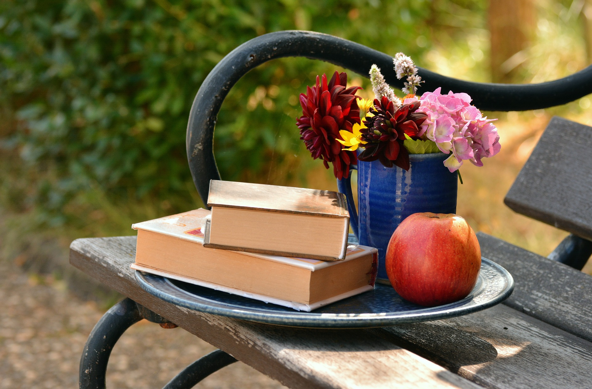 Image shows some books on a bench with a vase of flowers and an apple