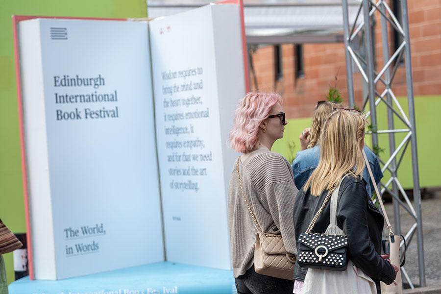 Image shows two women walking past a giant book at the Edinburgh Literary Festival