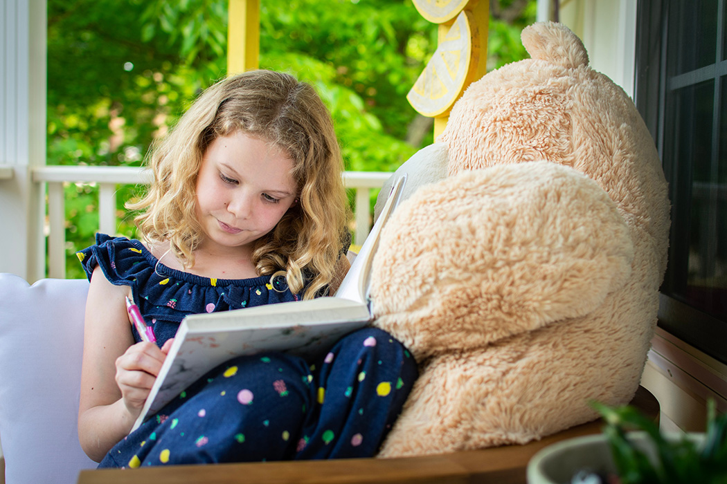 Image shows a photo of a young girl writing. She is sitting next to a giant teddy bear.