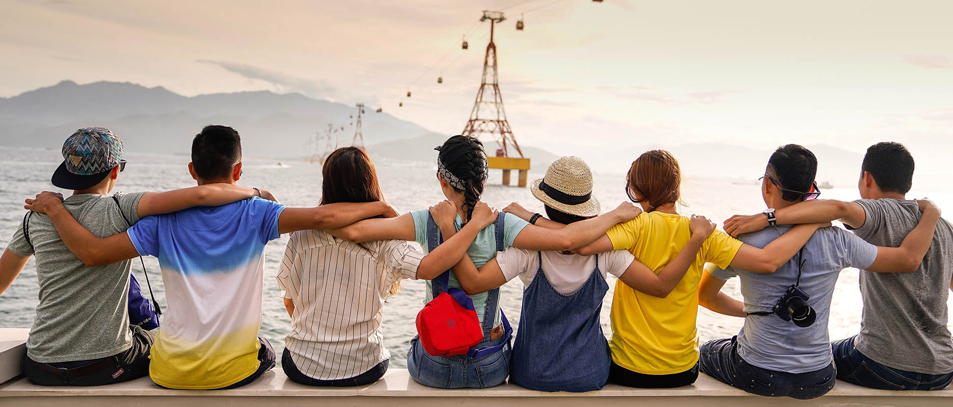 Images shows a group of people from behind, with their arms linked