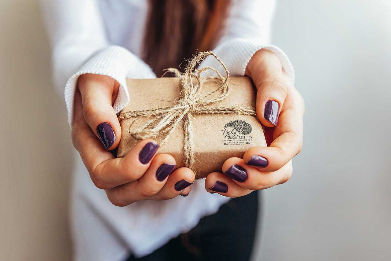 Woman holding a gift from PaisleyGroveGIFTS.com, gift wrapped with brown kraft paper.