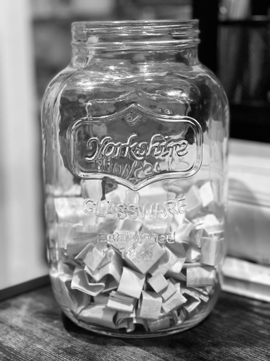 A black and white image of a gallon-sized mason jar from Yorkshire Glassware filled with small folded papers, sitting on a wood grain and metal desk, background blurred.