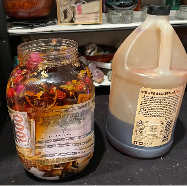 A photo of a gallon-sized mason jar, filled with flowers, gold leaf, ancestor money, and other materials, sitting on an altar covered with a black cloth, next to a one-quarter filled, 5 lb jug of organic honey.