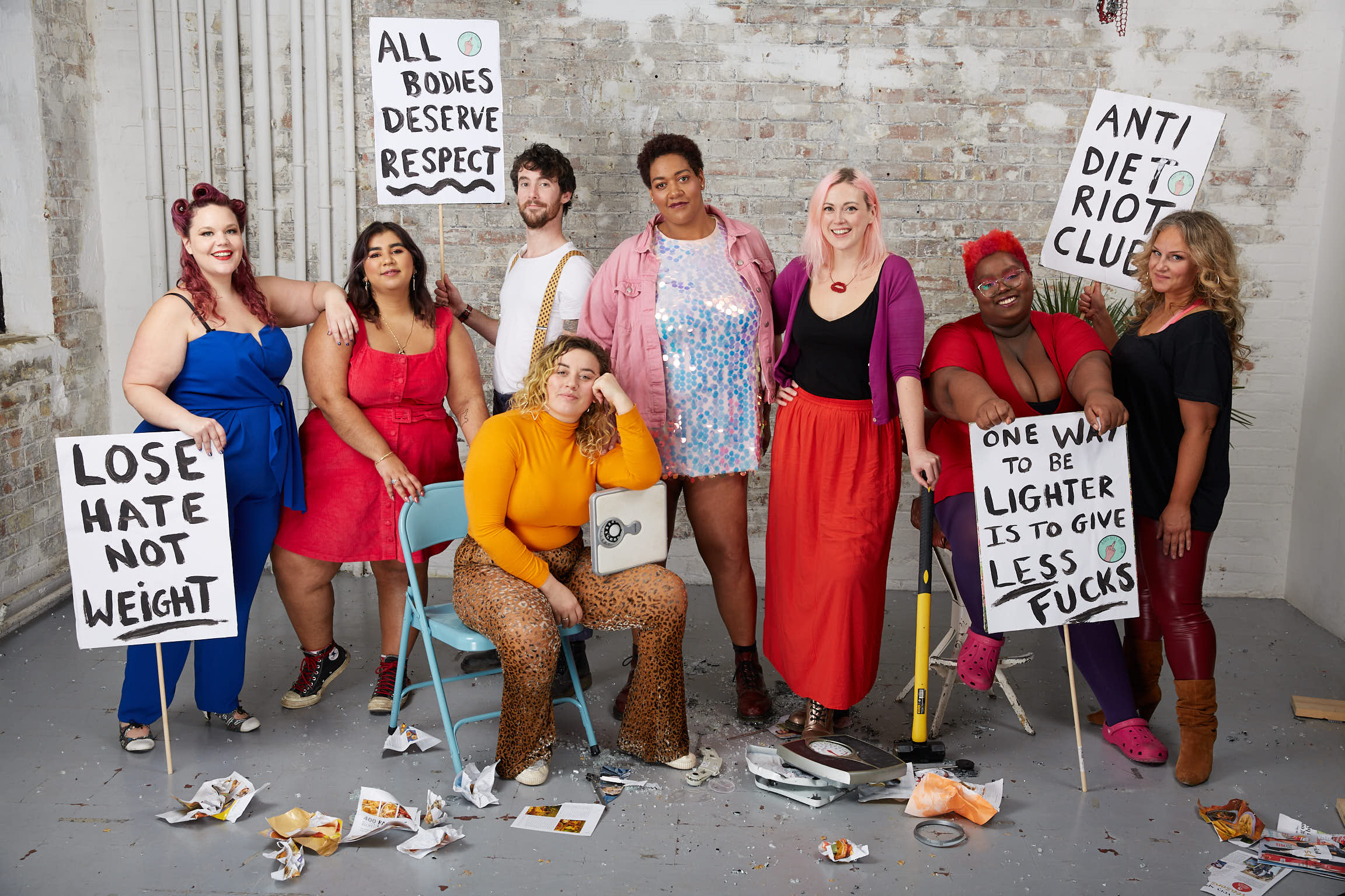 Members of the Anti Diet Riot Club Community standing in a group with protest signs