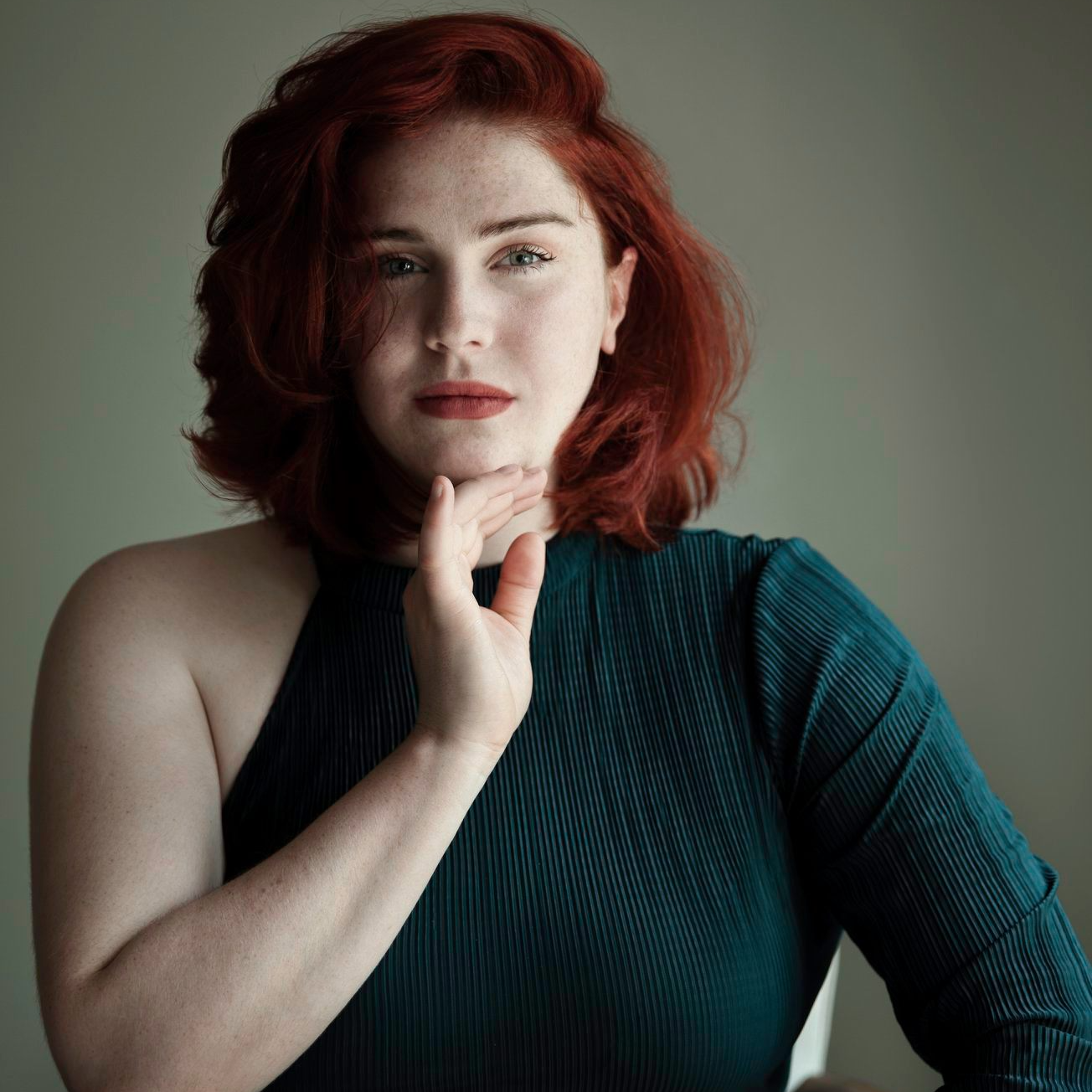 A still photo of Evie, a white woman with a glowing auburn bob hairstyle, dressed in an off the shoulder teal top, with her right hand underneath her chin. Staring straight into the camera against light grey background