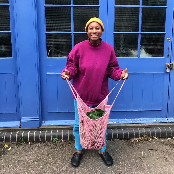 A photo a Kareem against a blue painted doors wearing a red jumper and yellow beanie hat. She's smiling widely and holding a pink netted bag full of ingredients excited to cook them!