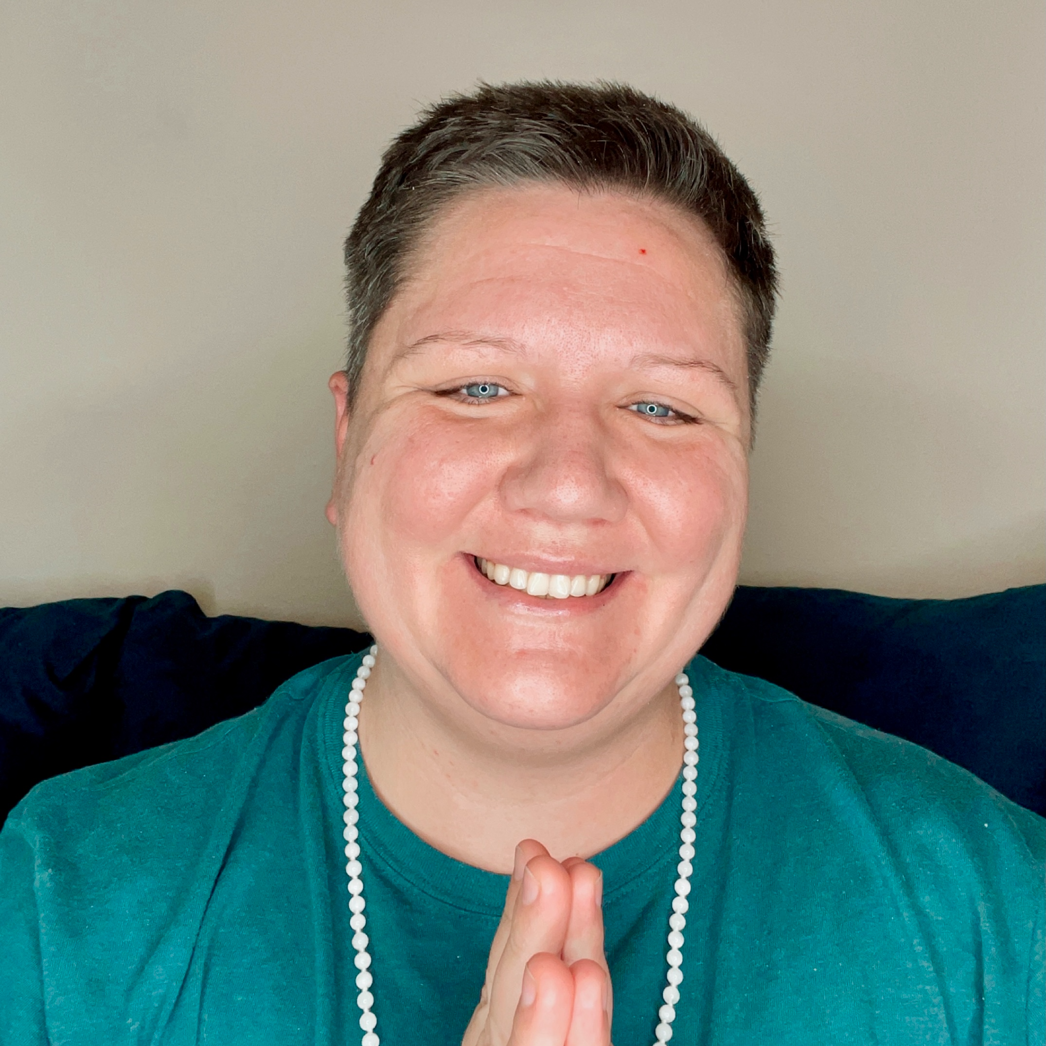 A still photo of Allé, a white non-binary, trans person with short grey/brown hair. They are standing in front of a white wall with the top of a sofa in the background, whilst wearing a teal green t-shirt and a white beaded necklace. Their fingertips are together in front of their chest and they are smiling showing his amazing teeth.