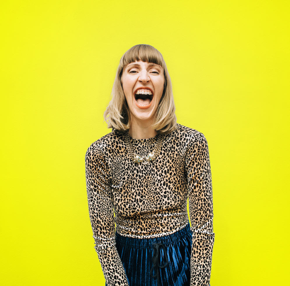 A still photo of Lacey, a white woman with a short blonde bob with a block fringe, she is standing in front of a lemon yellow background wearing a leopard print long sleeve top and teal bottoms. She has wide open smile showing all her fabulous teeth