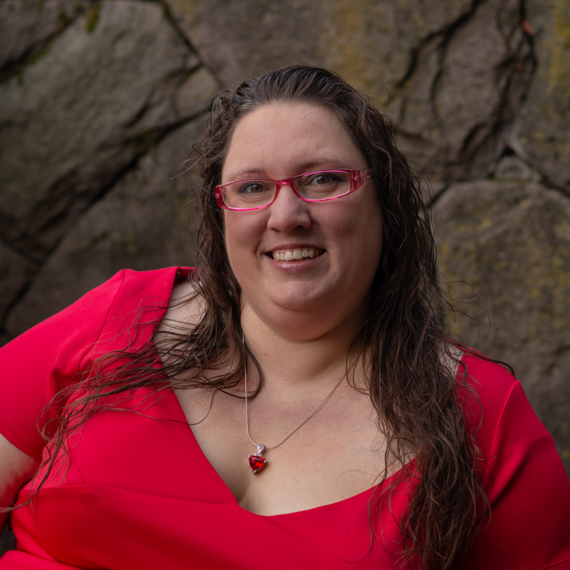 A photo of Ragen a white women, with long brown straight hair and wearing a red top whilst beautifully smiling against a stone wall