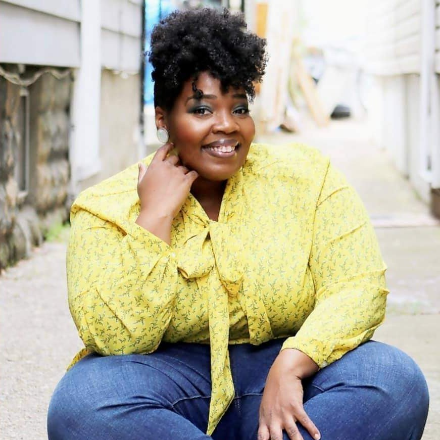 A still photo of Dr Joy a black woman, with pinned up curly hair wearing a sunshine yellow shirt sitting crossed legged on a street with a beaming smile