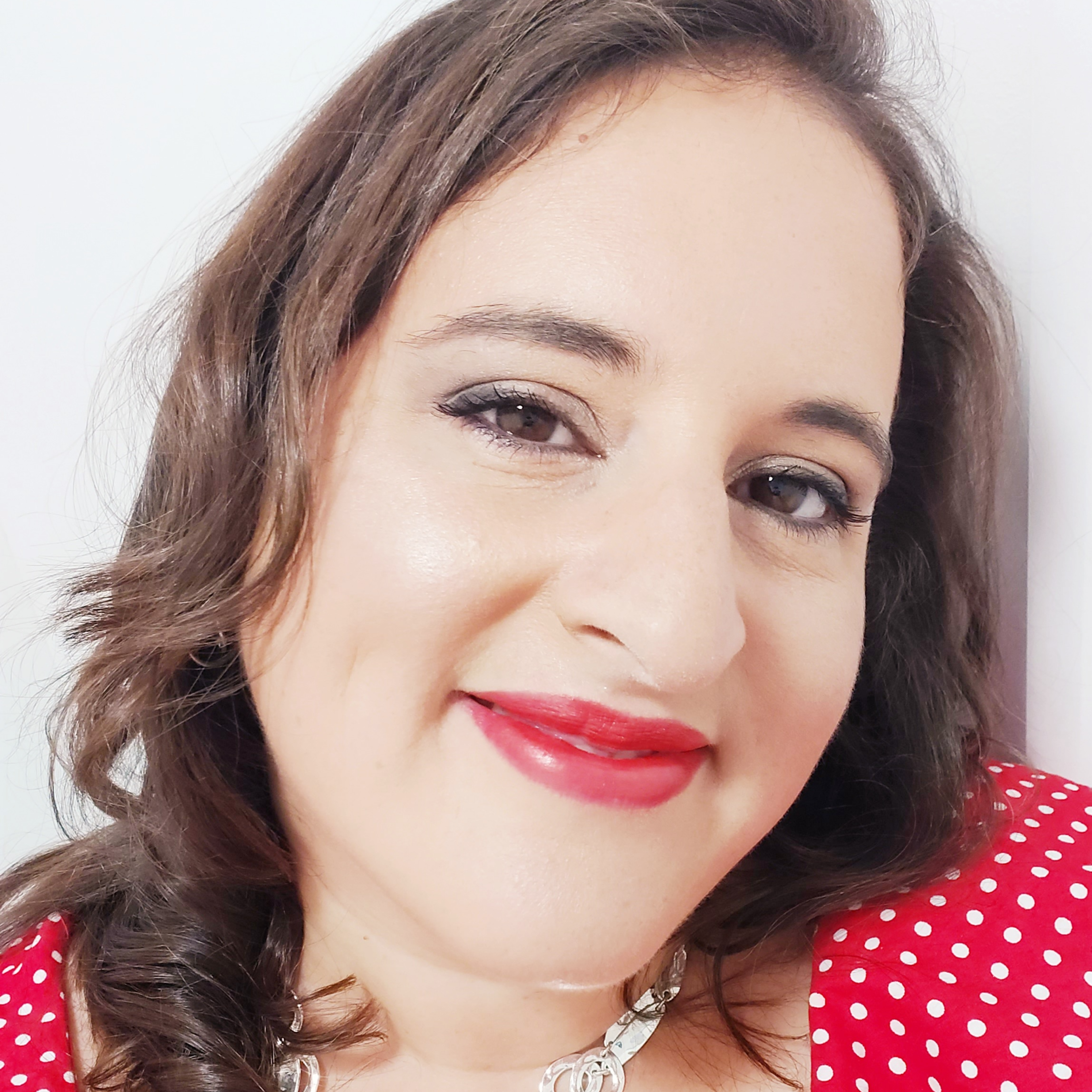 a still photo of Dr Natasha, a woman with brown mid length hair. She is wearing a red spotty top and a luscious red lipstick to match. Natasha is smiling with her head tilted to the side in front of a white background