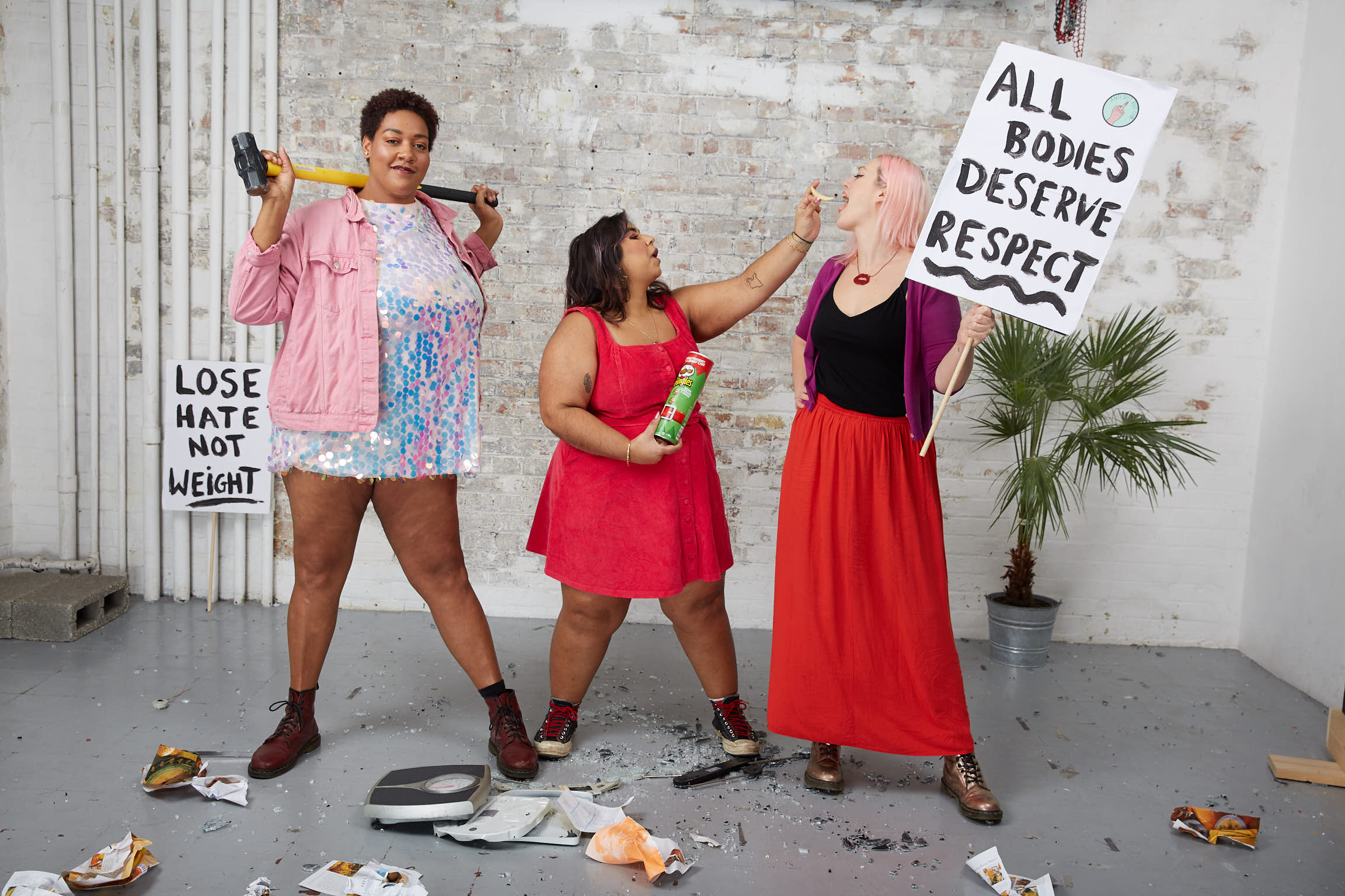 Members of the Anti Diet Riot Club Community having fun eating snacks with protest signs