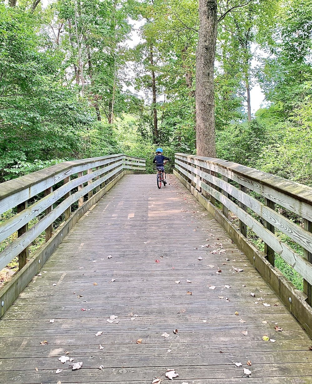 Boy riding a bike across a wooden bridge