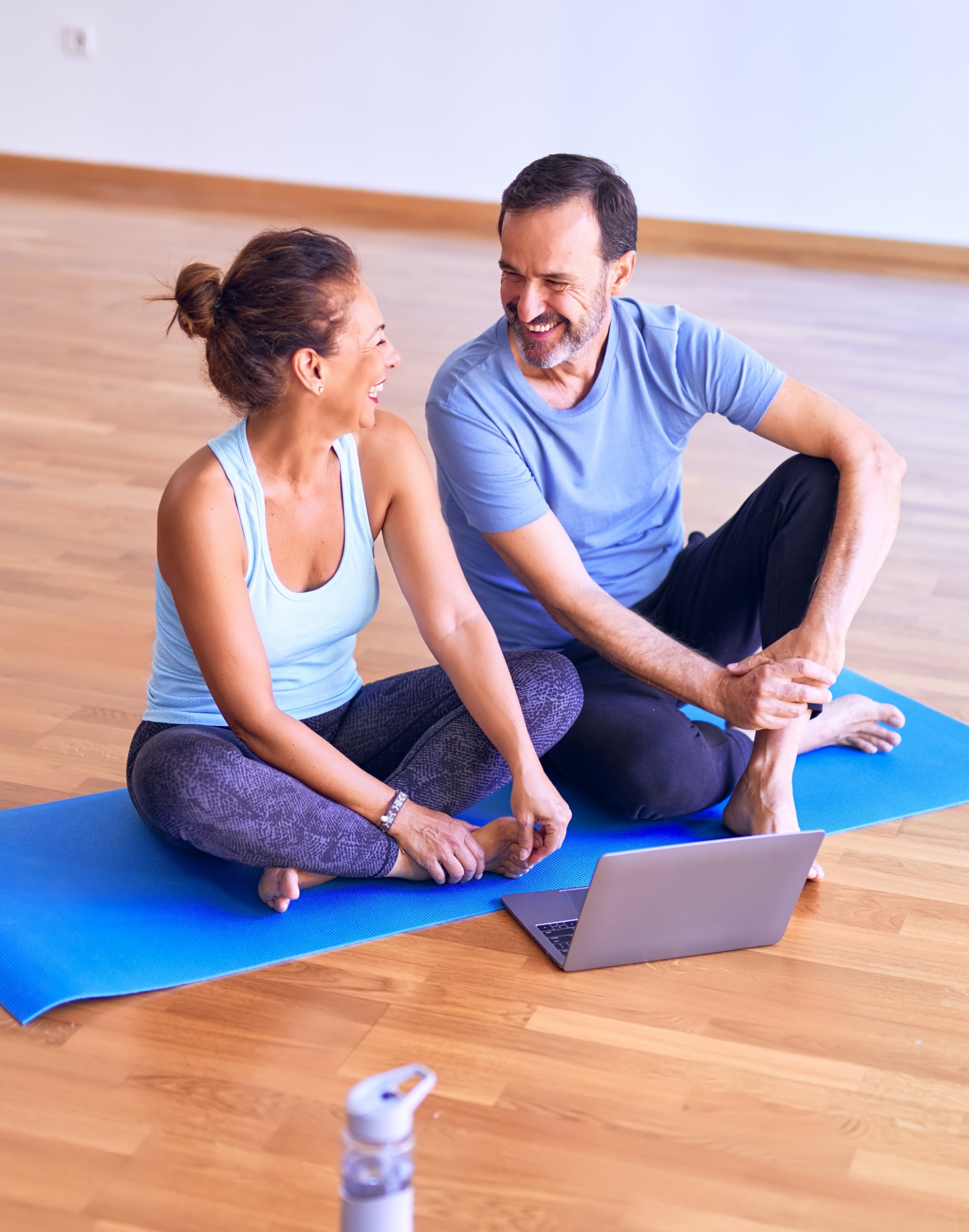 smiling man and woman on yoga mat evergreen wellness