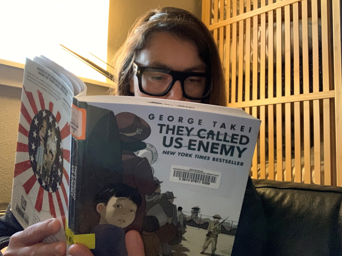 woman wearing glasses reading They Called Us Enemy by George Takei