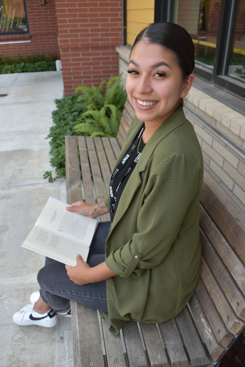 Lia Gutierrez reading on a bench