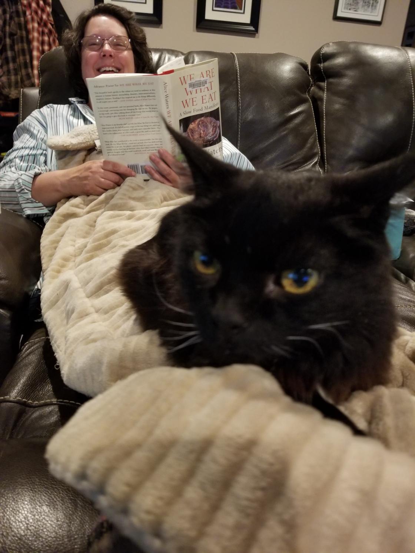 Susan Cackler reading under her cat
