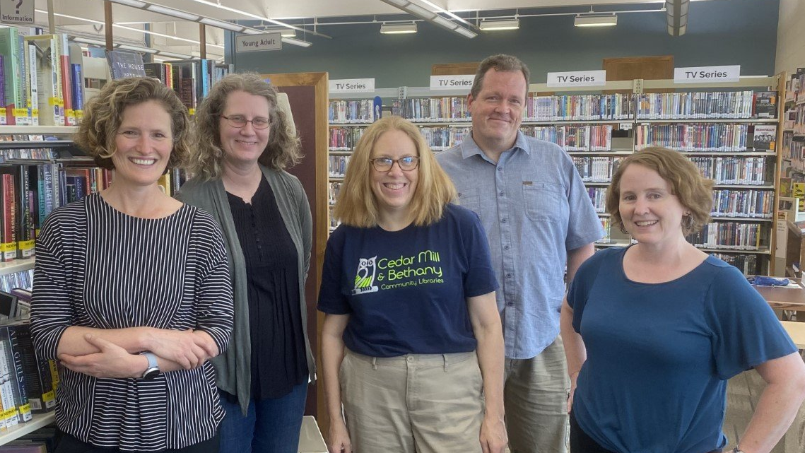 5 staff members from Cedar Mill Community Library smile for the camera in front of the book stacks