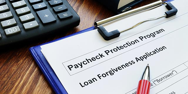 Paycheck protection program loan forgiveness application form on clipboard with pen