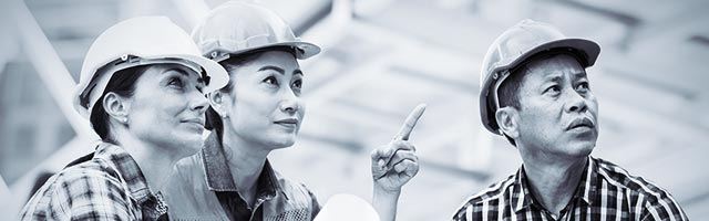 Two women and man wearing hard hats pointing at something