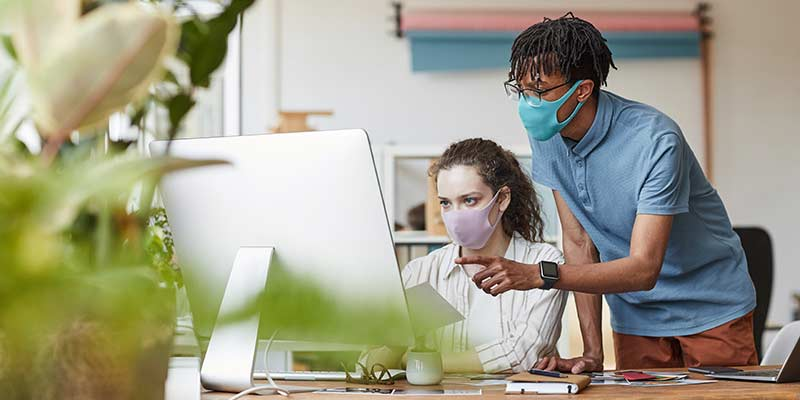 Workers wearing masks looking at computer screen together