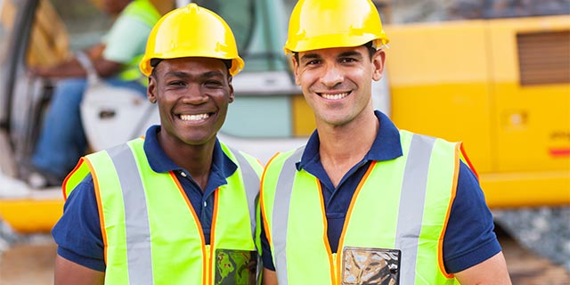 two construction workers in hard hats and vests smiling on job site