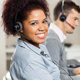 Smiling woman wearing phone headset working in office.