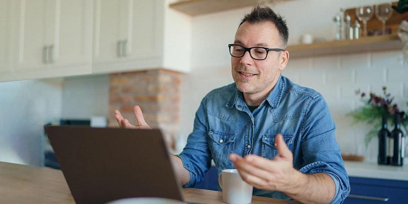 man in blue shirt gesturing towards laptop screen