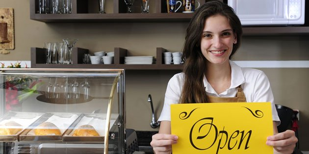 smiling woman standing behind counter holding open sign