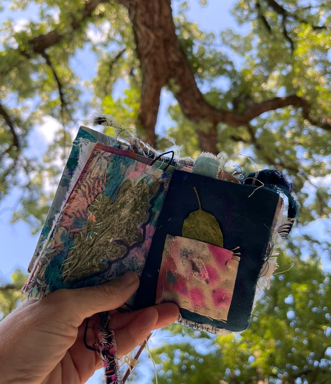 A handmade cloth book against an oak tree