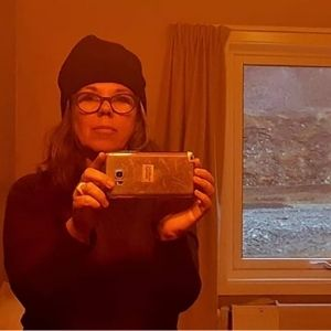 Andrea Annique Goldenberg taking a selfie with a red hue.