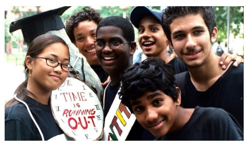 Group of students wearing a black t-shirt with a sign made to look like a clock that reads