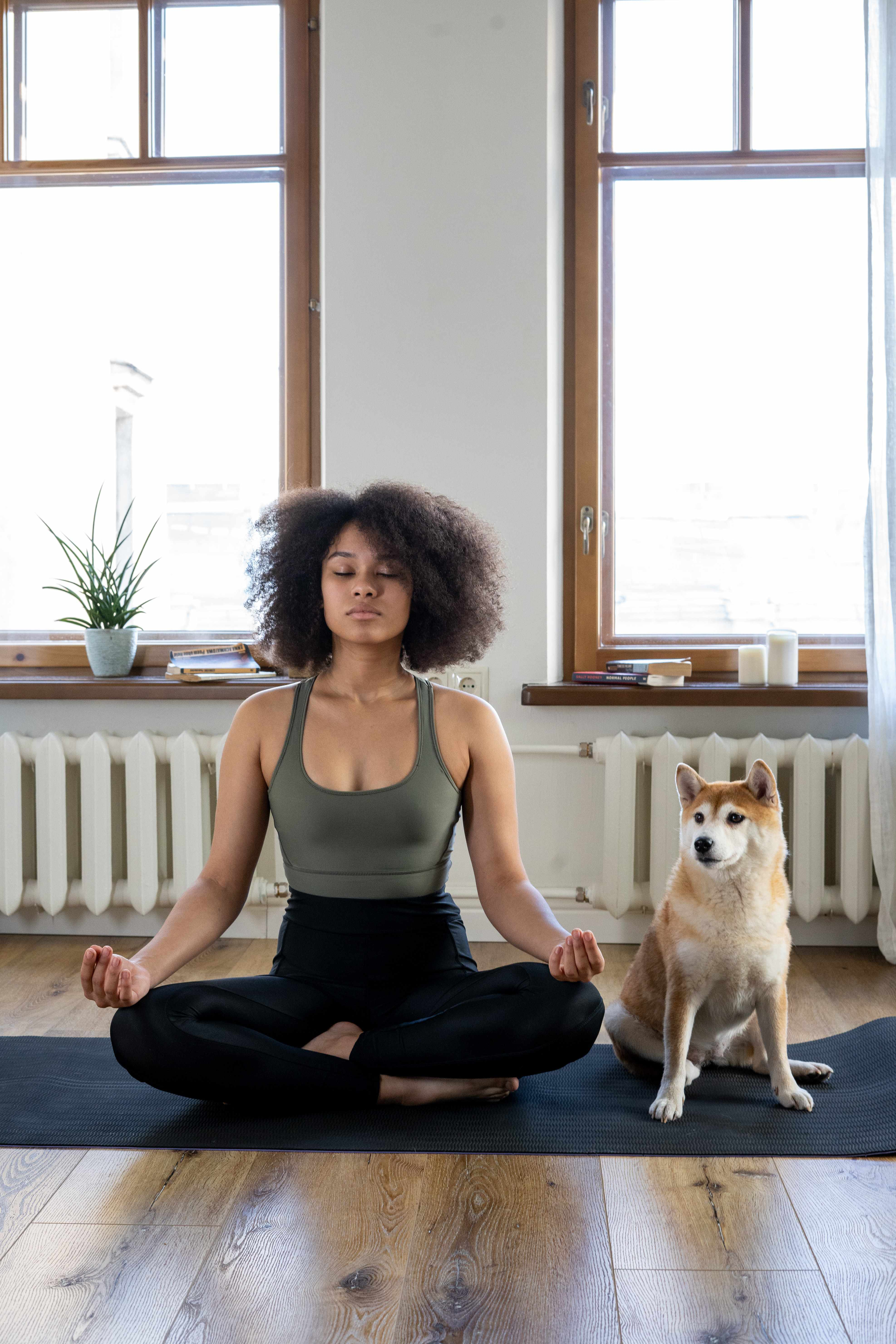 A young Black woman sitting on a yoga matt in a meditative pose, a dog sits next to her.