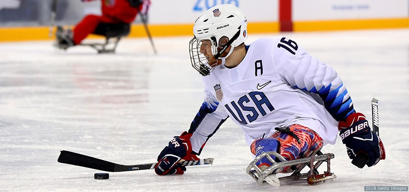 A white masculine presenting person with a white helmet, a white jersey with the letters USA and the number 16 on it, wearing red, blue and white pants, skating on adaptive sports equipments, playing hockey on an ice rink