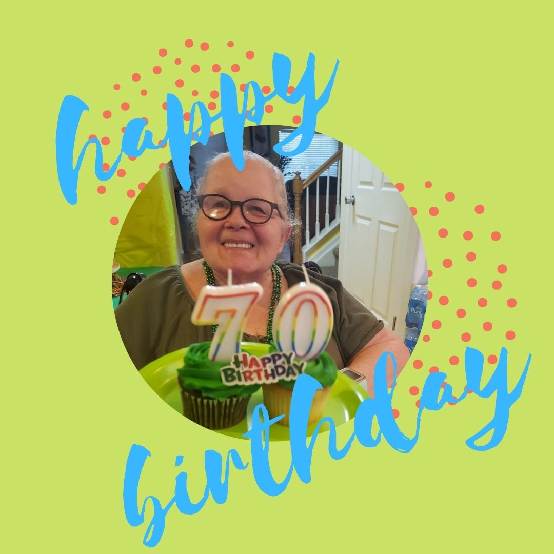 Katie is sitting in her chair, smiling, while someone is holding a plate with two cupcakes, with rainbow candles.  The candles are a seven and a zero to celebrate her 70th birthday. The background is green and there is blue text that reads 'Happy Birthday'