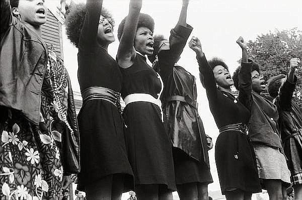 A black and white photo of seven Black women with their fists raised in the air.