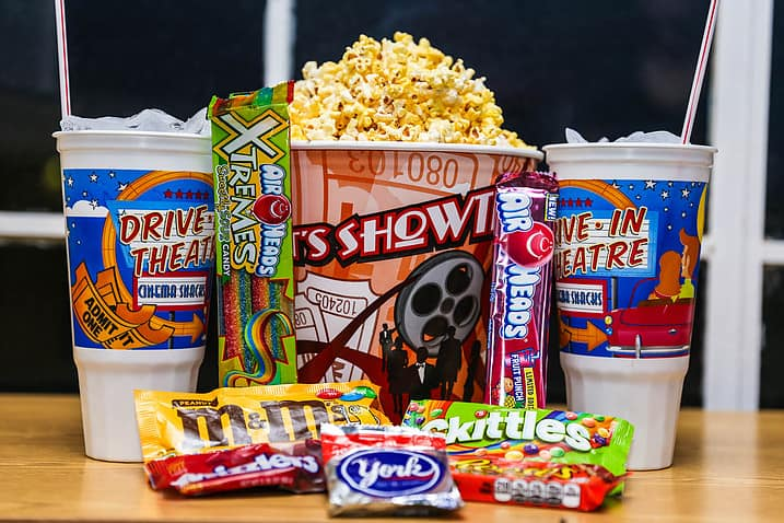 An image (from left  to right) A cup of soda with the words Drive in Theater Cinema Snacks with an image of Admit One tickets next to, Air Heads Xtremes Candy, a rainbow candy in a green package, next to a bucket of pop corn with the words It's Showtime and an image of a movie reel and an admit one ticket, next to another Air Heads candy in a pink wrapper, next to a similar cup of soda as teh first one, at the bottom of the image are M&Ms, Skittles, Twizzlers, York, and Reese's candy bars.