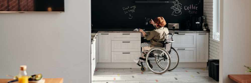 A white fem-presenting person in a wheelchair with short red hair wearing a long sleeved olive shirt, a black and white skirt, and white shoes making coffee in a universal accessible kitchen with white cabinets and a black wall.
