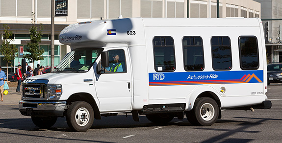 White Access-a-Ride bus driving downtown