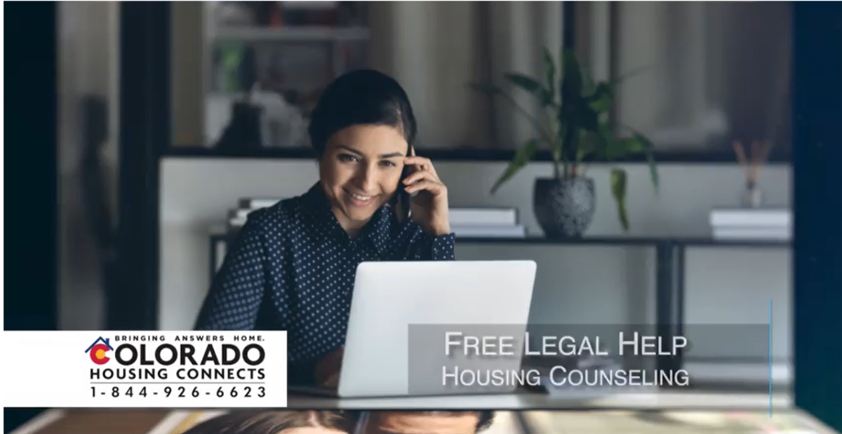 A photo of a light skinned woman in a kitchen wearing a black shirt with white polka dots, she has dark hair in a bun, she is on the phone and sitting in front of a laptop. The words Free Legal Help Housing Counseling is located in the bottom right corner, and the words