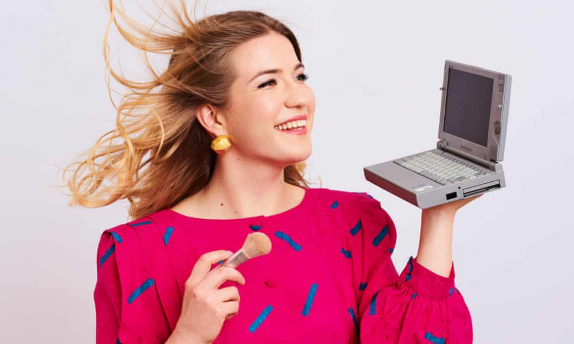 An image of a blonde woman wearing a pink shirt with black lines on it holding a small laptop